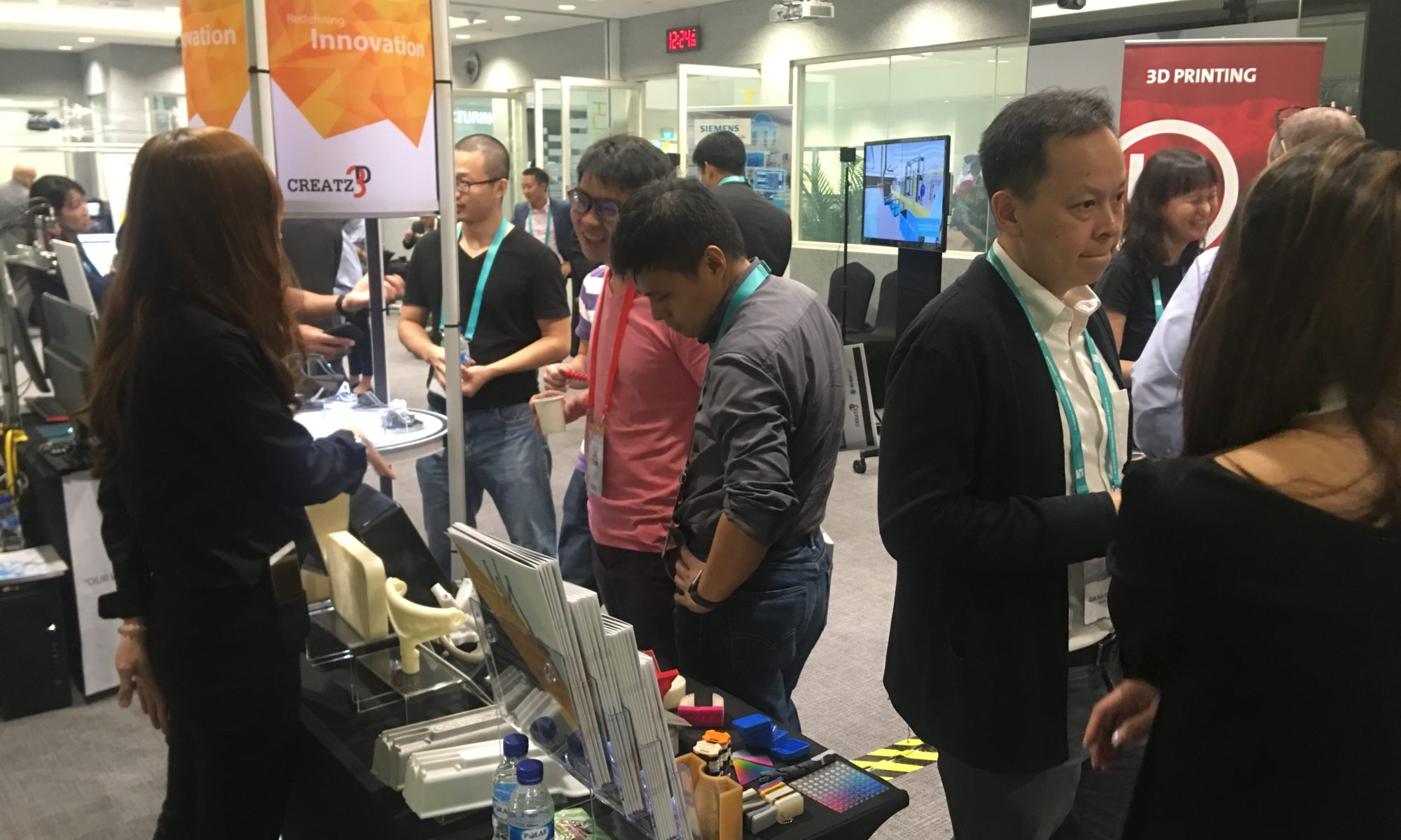 Visitors learning about 3D printing solutions at Creatz3D's booth at ARTC Model Factory launch event