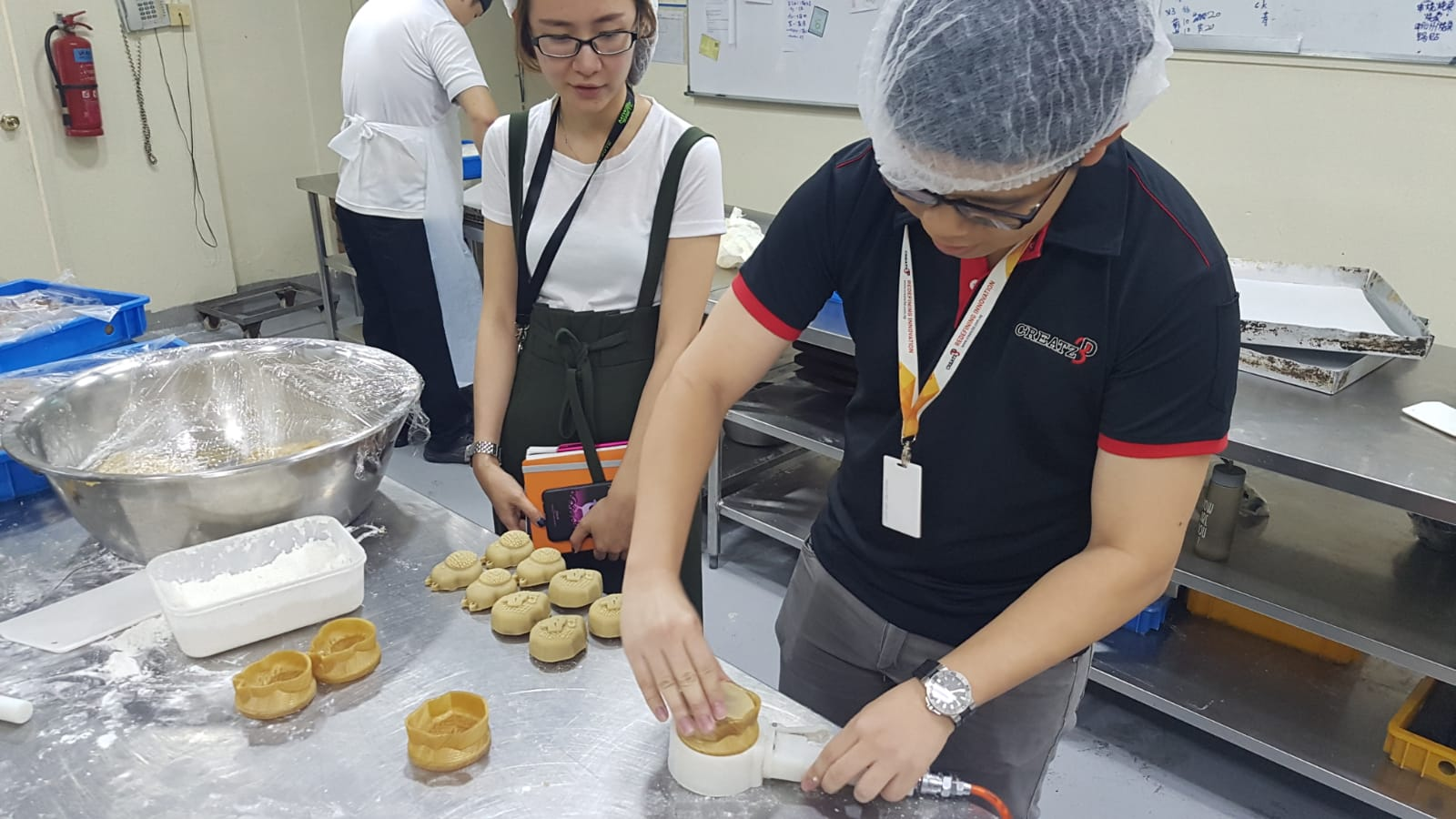 Ms. Nijie and Mr. Zhisheng having a go at making mooncakes with 3D printed molds.