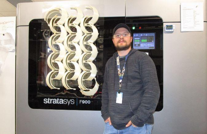 Joshua Dunn, an additive manufacturing subject matter expert, stands with a batch of face shield frames that were produced with a Stratasys F900 3D printer.