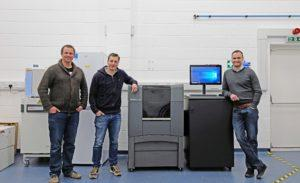 Dr Colin Barker, Richard Vellacott and Nick Rollings (left to right) standing next to Stratasys J826