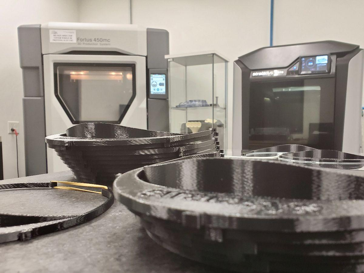 Stratasys FDM 3D printers (background) at Don Schumacher Racing are operating 24 hours a day to produce headbands for medical face shields.
