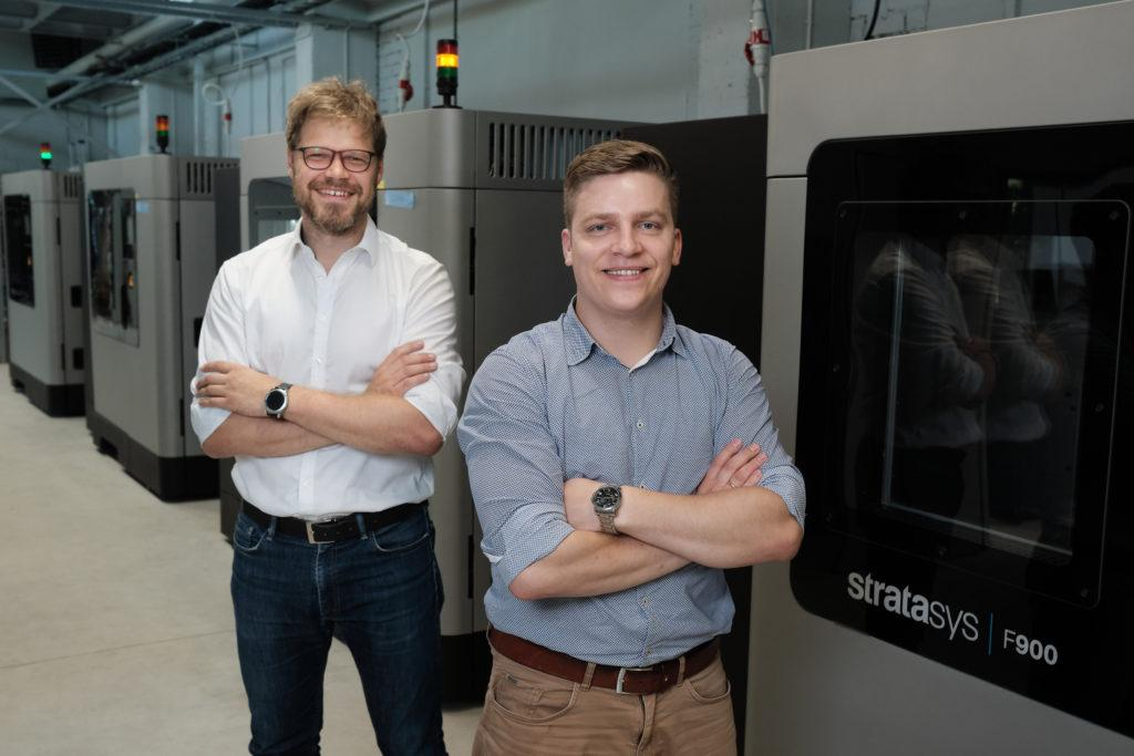 AM Craft co-founders Didzis Dejus and Jānis Jātnieks standing alongside Stratasys F900 3D printers.